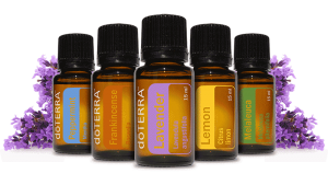 5 Bottles of doterra essential oil with sprigs of lavendar behind